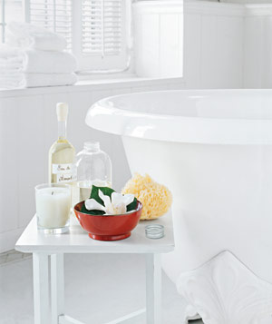 White bathroom with clawfoot bathtub and relaxing oils, flowers and candles on a table