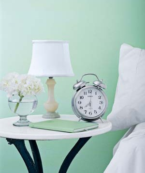 Bedside table with alarm clock, lamp and flowers