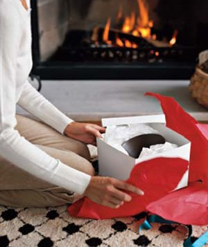 Woman unwrapping a gift in front of a fireplace