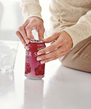 Woman with manicured nails opening can of soda