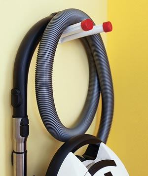 Vacuum cleaner hose hung on a hook