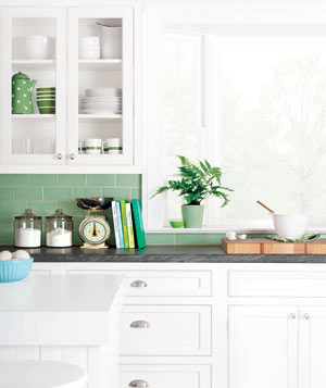 A clean and organized white kitchen with a big window and a green tile backsplash