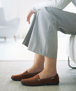 Woman wearing brown shoes and grey pants