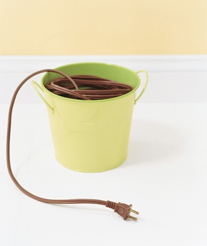 Extension cords stored in a large bucket