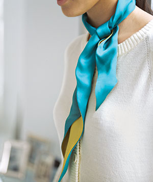 Woman wearing a white sweater and teal scarf
