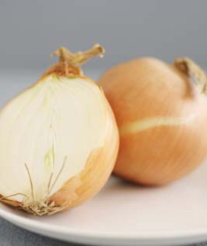 An onion cut in half on a white plate