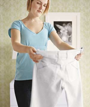 Woman holding up a pair of white pants