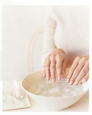Woman dipping her hand in a bowl of ice water
