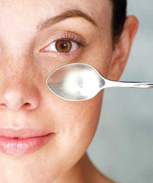 Woman holding a spoon to her face