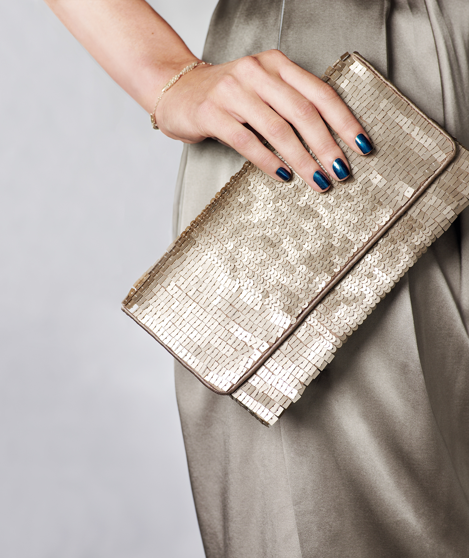 Woman with a dark blue manicure holding a clutch