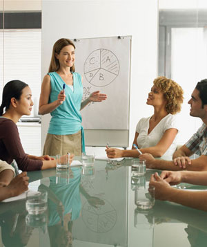 Woman standing at chart presenting to colleagues around table, smiling