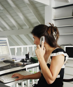 Woman talking on the phone and checking her computer