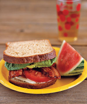 BLT sandwich and watermelon slice on a plate