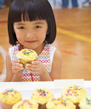 Little girl with cupcakes