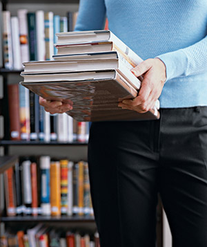 Woman in a library carries books