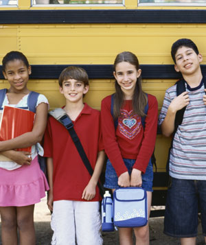 Children standing in front of a school bus