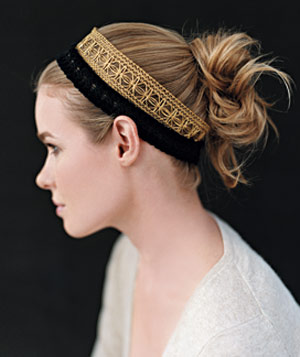 Profile of a woman with hair up in a gold and black headband