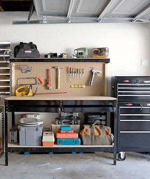 Inexpensive pegboard mounted to the wall neatly displays tools at eye level.