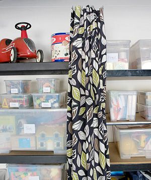 Hang wire and curtain panels to prettily hide storage bins at a moment's notice.
