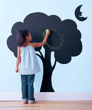 Young girl writing on wall with chalboard painted mural