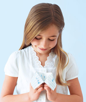 Young girl with a paper origami fortune teller