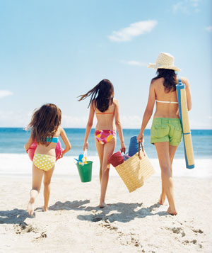 Woman with two girls walking at the beach