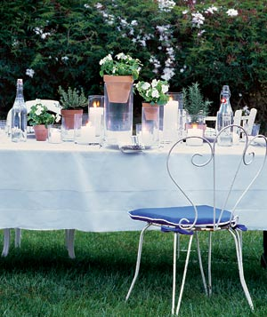 Outdoor dining table with candles and place setting