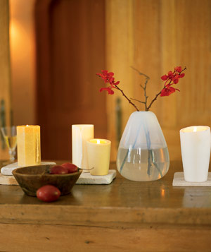 Dining table decorated with lit candles and a clear teardrop vase