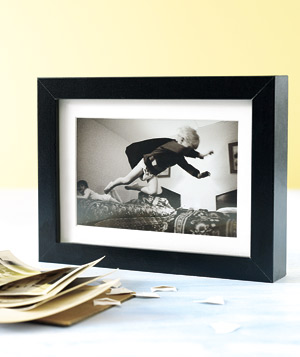 Black and white photograph of boy pretending to be a superhero in a black frame