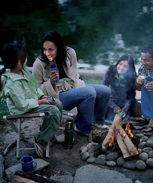 Family telling a ghost story by a campfire