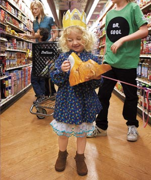 Little girl wearing a crown in a grocery store