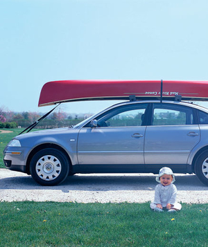 Canoe strapped on car roof and a baby sitting on the grass beside it