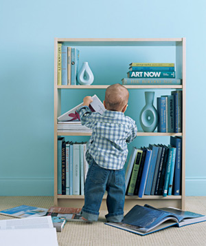 Toddler pulling things off bookcase onto floor