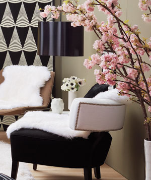 Sheep skin rug, flowering branches, and plum pendant lamp in living room.