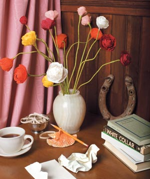 A table with a vase of paper flowers