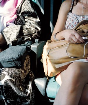 Two women sitting side by side with purses in their laps