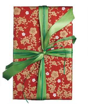 Gift wrapped in red paper with three green ribbons