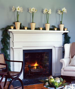 A row of white votives on a fireplace mantel