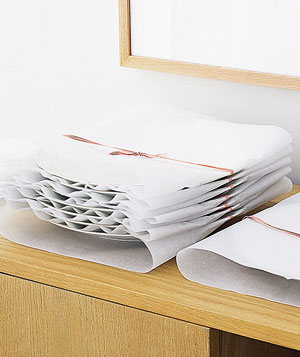 Stack of dishes wrapped in parchment paper and ribbon