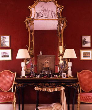 Elegant room with deep red walls, gold-framed antique mirror and red antique chairs