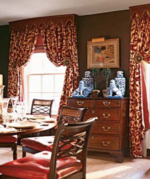 Dining room with heavy patterned red drapes and wooden chairs with red seats