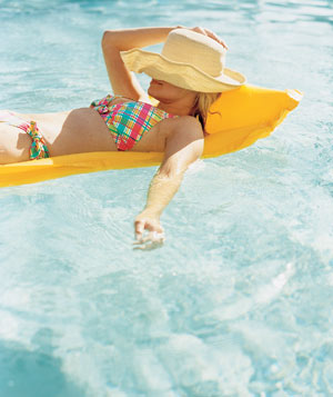 Woman in plaid bikini and sun hat floating on a yellow floatie in pool