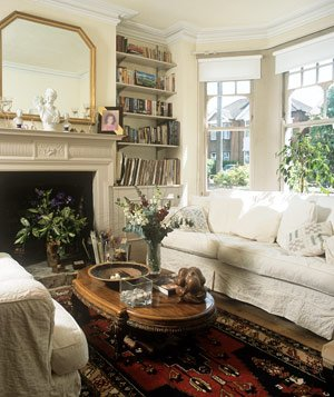 Traditional Edwardian style cozy living room with white sofas and fireplace
