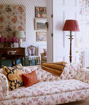 Living room with pink floral wallpaper, upholstered sofa and lamp