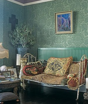 A traditional living room in green with pattern wallpaper and vintage wrought iron sofa