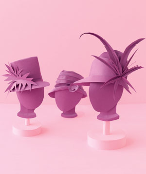 Paper construction of hats on mannequins by Matthew Sporzynski