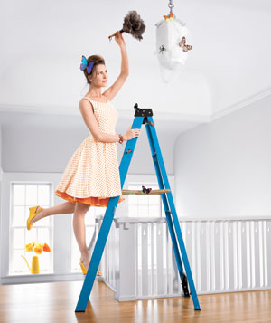 Woman dusting a lighting fixture