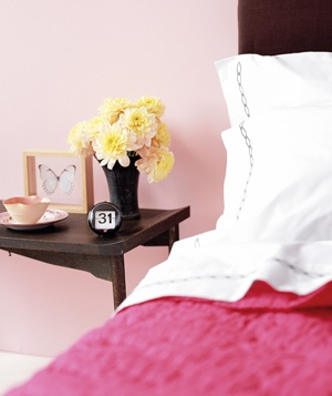 Bed and night stand with bouquet of flowers and calendar