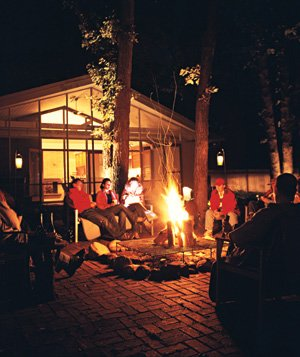 Guests at an outdoor party lit by a patio fire pit