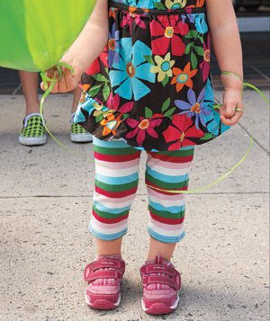 Girl in a flowered dress with striped leggings